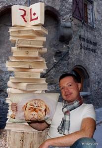 Kollege Roland Hölzl mit Bücherturm und Hundepolster